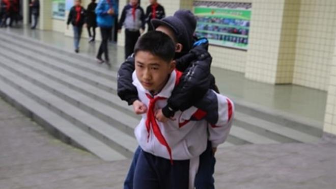 A hátán viszi az iskolába mozgássérült barátját a 12 éves kisfiú